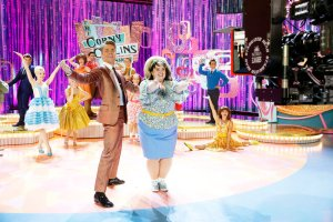 HAIRSPRAY LIVE! -- BTS Promo -- Pictured: (l-r) Dove Cameron as Amber Von Tussle, Derek Hough as Corny Collins, Maddie Baillio as Tracy Turnblad -- (Photo by: Trae Patton/NBC)